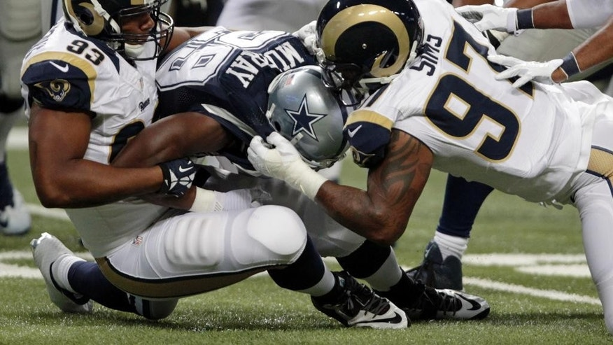 Dallas Cowboys running back DeMarco Murray, center, is stopped by St. Louis Rams defensive tackle Ethan Westbrooks, left, and defensive end Eugene Sims during the second quarter of an NFL football game Sunday, Sept. 21, 2014, in St. Louis. (AP Photo/Tom Gannam)