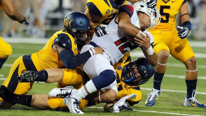 California defenders tackle Arizona quarterback Anu Solomon (12) during the first half of an NCAA college football game, Saturday, Sept. 20, 2014, in Tucson, Ariz. (AP Photo/Rick Scuteri)
