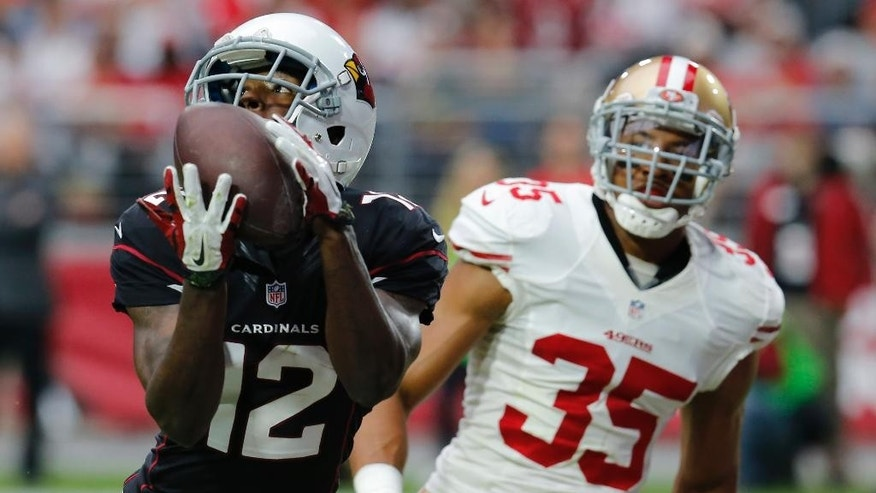 Arizona Cardinals wide receiver John Brown (12) scores a touchdown as San Francisco 49ers free safety Eric Reid (35) defends during the second half of an NFL football game, Sunday, Sept. 21, 2014, in Glendale, Ariz. (AP Photo/Rick Scuteri)