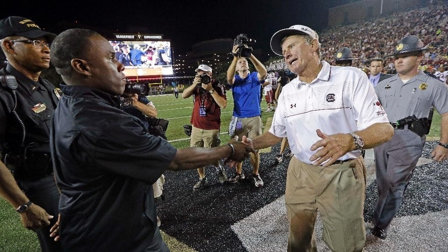"South Carolina head coach Steve Spurrier , right, shakes hands with Vanderbilt head coach Derek Mason after South Carolina's win over Vanderbilt in an NCAA college football game Saturday, Sept. 20, 2014, in Nashville, Tenn. South Carolina won 48-34 to give Spurrier his 202nd Southeastern Conference win, breaking a tie with Vince Dooley and putting him second only to Paul ""Bear"" Bryant, who has 292. (AP Photo/Mark Humphrey)"