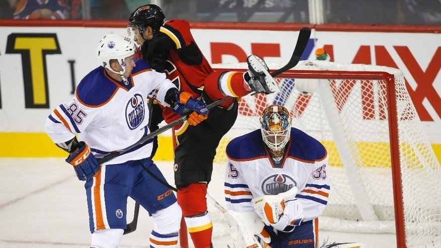 Edmonton Oilers goalie Viktor Fasth, right, from Sweden, makes a save as Calgary Flames Devin Setoguchi, center, has his leg lifted by Oilers Martin Marincin, from Slovakia, during the second period of an NHL preseason hockey game in Calgary, Alberta, Sunday, Sept. 21, 2014. (AP Photo/The Canadian Press, Jeff McIntosh)