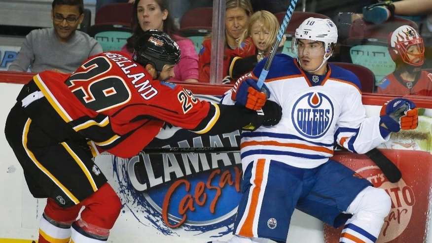 Edmonton Oilers' Nail Yakupov, right, from Russia, dodges a check from Calgary Flames' Deryk Engelland during the second period of an NHL preseason hockey game in Calgary, Alberta, Sunday, Sept. 21, 2014. (AP Photo/The Canadian Press, Jeff McIntosh)