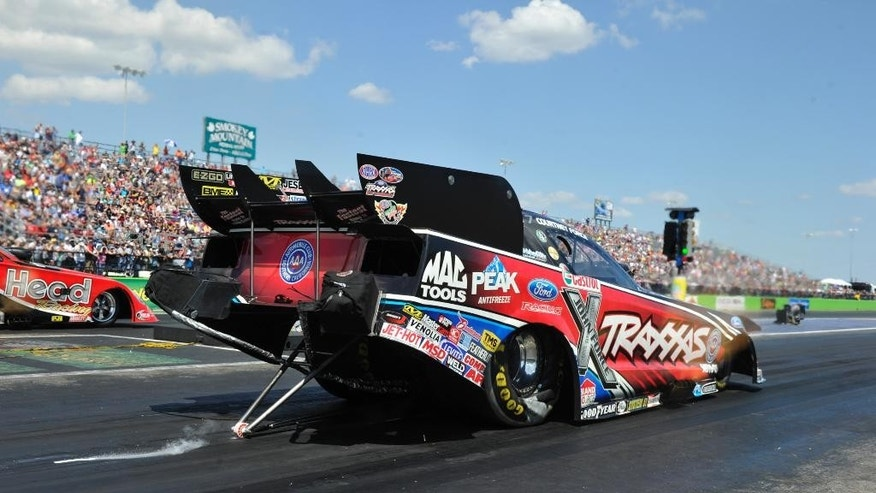 In this photo provided by NHRA, Courtney Force races to her fourth No. 1 qualifying position of the season in Funny Car on Saturday, Sept. 20, 2014, at the AAA Texas NHRA FallNationals drag races at the Texas Motorplex in Ennis, Texas. (AP Photo/NHRA, Robert Grice)