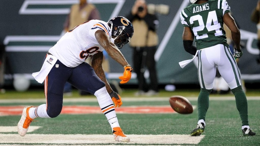Chicago Bears tight end Martellus Bennett (83) spikes the ball after catching a touchdown pass against New York Jets defensive back Phillip Adams (24) in the third quarter of an NFL football game, Monday, Sept. 22, 2014, in East Rutherford, N.J. (AP Photo/Bill Kostroun)