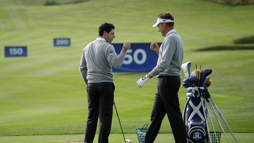 Europe's Rory McIlroy, left, and Ian Poulter perform a fist bump as they greet each other on the driving range ahead of the start of the Ryder Cup golf tournament in Gleneagles, Scotland, Monday, Sept. 22, 2014.  The U.S. team arrives for the Ryder Cup Monday, with the tournament  starting on Friday.  (AP Photo/Matt Dunham)