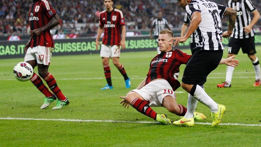 Juventus's Carlos Tevez, right, scores a goal as AC Milan's Ignazio Abate tries to stop him during the Serie A soccer match between AC Milan and Juventus at the San Siro stadium in Milan, Italy, Saturday, Sept. 20, 2014. (AP Photo/Antonio Calanni)
