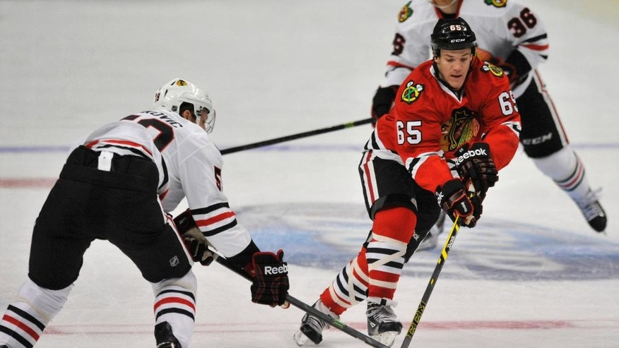 Chicago Blackhawks' Andrew Shaw (65), battles Zach Miskovic (59), for the puck during the first period of a team scrimmage during Chicago Blackhawks Training Camp Festival in Chicago, Monday, Sept. 22, 2014. (AP Photo/Paul Beaty)