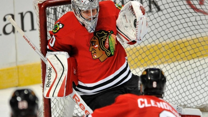 Chicago Blackhawks goalie Corey Crawford makes a save during the first period of a team scrimmage during Chicago Blackhawks' Training Camp Festival in Chicago, Monday, Sept. 22, 2014. (AP Photo/Paul Beaty)