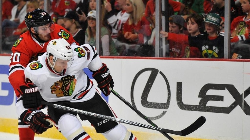 Chicago Blackhawks' Brandon Saad (20), battles  Zach Miskovic (59), for a loose puck during the first period of a team scrimmage during Chicago Blackhawks' Training Camp Festival in Chicago, Monday, Sept. 22, 2014. (AP Photo/Paul Beaty)