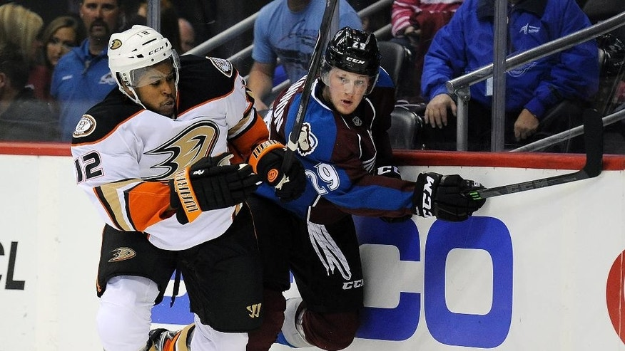 Anaheim Ducks right wing Devante Smith-Pelly, left, and Colorado Avalanche center Nathan MacKinnon, right, fight for the puck in the first period of an NHL preseason hockey game Monday, Sept. 22, 2014 in Denver. (AP Photo/Chris Schneider)