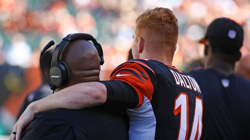 Cincinnati Bengals quarterback Andy Dalton (14) puts his arm around offensive coordinator Hue Jackson in the closing seconds of their 33-7 win over the Tennessee Titans in an NFL football game, Sunday, Sept. 21, 2014, in Cincinnati. (AP Photo/David Kohl)