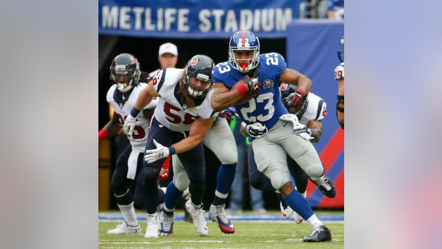 New York Giants running back Rashad Jennings (23) is tackled by the Houston Texans in the third quarter of an NFL football game, Sunday, Sept. 21, 2014, in East Rutherford, N.J. (AP Photo/Kathy Willens)