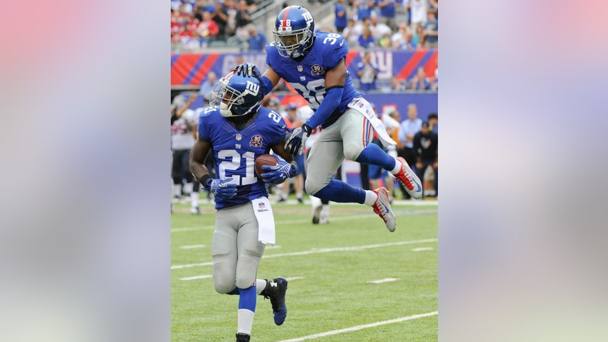 New York Giants cornerback Dominique Rodgers-Cromartie (21) and cornerback Trumaine McBride (38) celebrate after Rodgers-Cromartie intercepted a pass against the Houston Texans in the fourth quarter of an NFL football game, Sunday, Sept. 21, 2014, in East Rutherford, N.J. (AP Photo/Bill Kostroun)