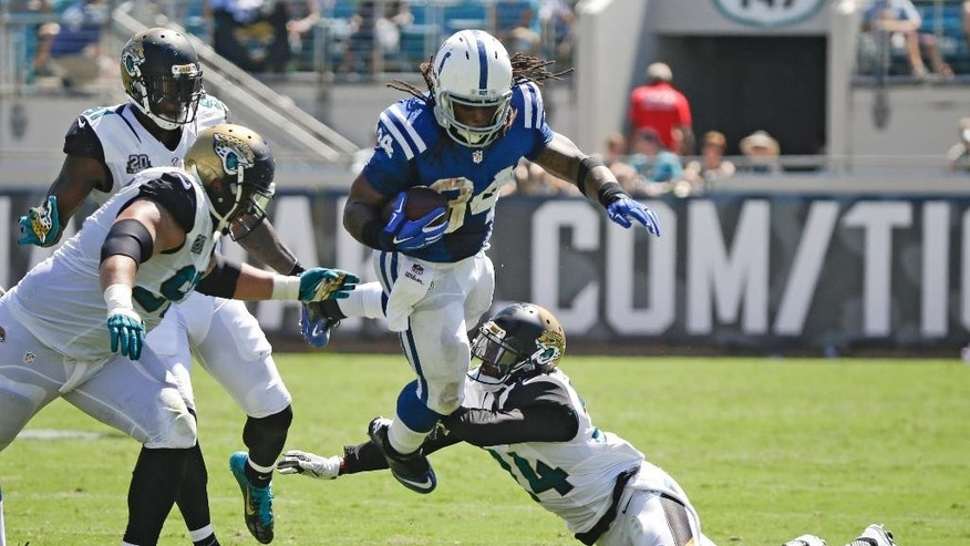 Indianapolis Colts running back Trent Richardson (34) leaps as he tries to get between Jacksonville Jaguars defensive end Chris Clemons, far left, defensive tackle Roy Miller, left, and cornerback Will Blackmon, right, during the first half of an NFL football game in Jacksonville, Fla., Sunday, Sept. 21, 2014. (AP Photo/Stephen B. Morton)
