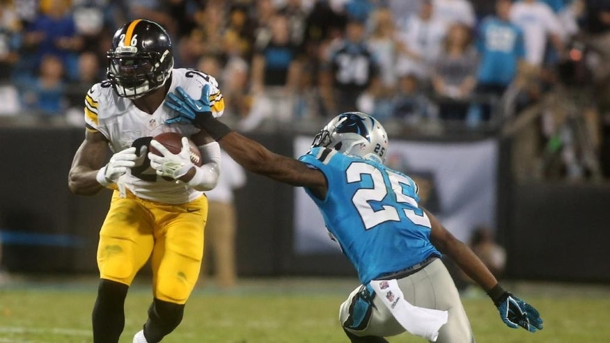 Pittsburgh Steelers' Le'Veon Bell (26) escapes the extended arm of Carolina Panthers' Bene Benwikere (25) during an NFL football game Sunday, Sept. 21, 2014, in Charlotte, N.C. (AP Photo/The Star, Ben Earp)