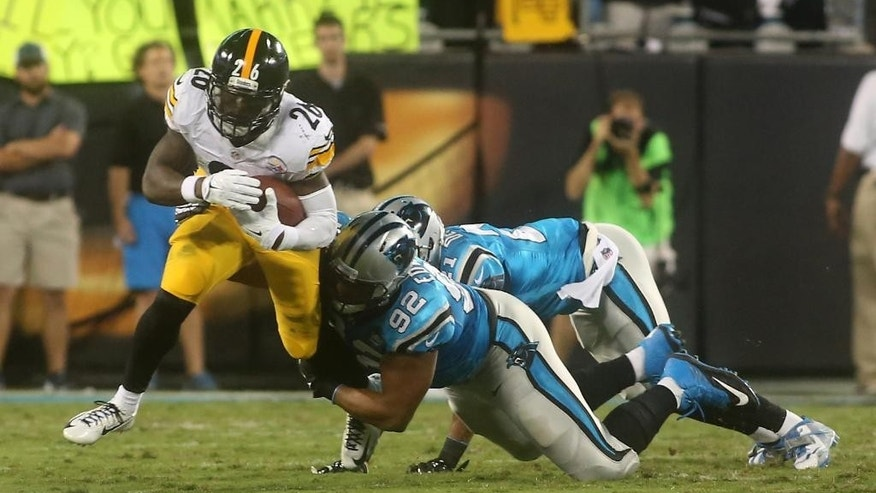 Pittsburgh Steelers' Le'Veon Bell (26) is brought down by Carolina Panthers'  Dwan Edwards (92) and Thomas DeCoud (21) during an NFL football game Sunday, Sept. 21, 2014, in Charlotte, N.C. (AP Photo/The Star, Ben Earp)