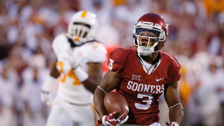 FILE - In this Sept. 13, 2014, file photo, Oklahoma wide receiver Sterling Shepard (3) carries during an NCAA college football game against Tennessee in Norman, Okla. With all the hype about freshman running back Samaje Perine, Sterling Shepard was an afterthought during Oklahoma's win over West Virginia. The junior has been the Sooners' most consistent offensive player, and he's coming off his third game with at least 100 yards receiving. (AP Photo/Sue Ogrocki, File)