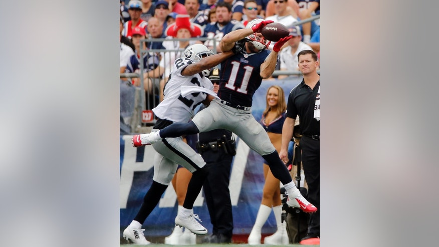 New England Patriots wide receiver Julian Edelman (11) catches a pass in front of Oakland Raiders cornerback Carlos Rogers (27) in the second half of an NFL football game Sunday, Sept. 21, 2014, in Foxborough, Mass. (AP Photo/Elise Amendola)