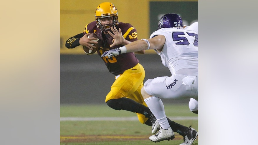FILE - In this Aug. 28, 2014, file photo, Arizona State quarterback Taylor Kelly tries to avoid Weber State tackle Jake Gallegos (57) during the first half of an NCAA college football game in Tempe, Ariz. The game between Arizona State and UCLA has decided the Pac-12 South champion each of the past two seasons. The 15th-ranked Sun Devils head into this year's showdown without quarterback Taylor Kelly and not knowing if Bruins quarterback Brett Hundley will play. (AP Photo/Matt York, File)