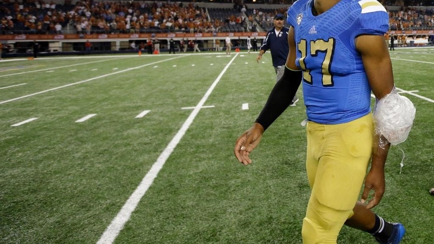 FILE - In this Sept. 13, 2014, file photo, UCLA quarterback Brett Hundley leaves the field  after UCLA defeated Texas 20-17 in an NCAA college football game in Arlington, Texas. The game between Arizona State and UCLA has decided the Pac-12 South champion each of the past two seasons. The 15th-ranked Sun Devils head into this year's showdown without quarterback Taylor Kelly and not knowing if Bruins quarterback Brett Hundley will play. (AP Photo/Tony Gutierrez, File)
