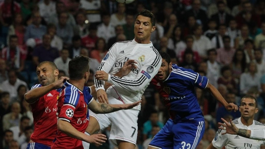Real's Cristiano Ronaldo, center, in action with Basel's Mohamed Elneny, right, during a Champions League final Group B soccer match between Real Madrid and FC Basel at the Santiago Bernabeu stadium in Madrid, Spain, Tuesday, Sept. 16, 2014. (AP Photo/Gabriel Pecot)