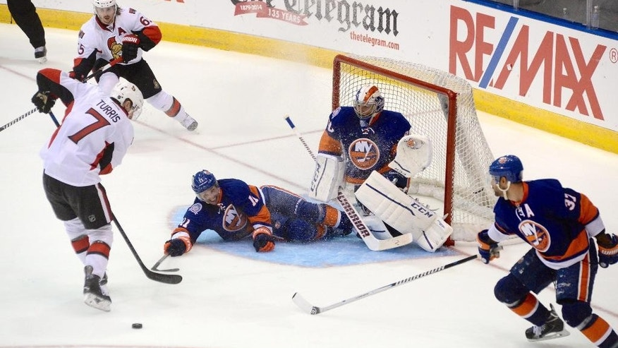 Ottawa Senators Kyle Turris tries to recover a puck as N.Y. Islanders Lubomir Visnovsky slide into his goalie Kevin Poulin during third period pre-season NHL action in St.John's, Newfoundland and Labrador, on Monday, Sept. 22, 2014. (AP Photo/The Canadian Press, Keith Gosse)