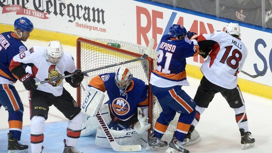 The puck bounces in front of N.Y. Islanders goalie Kevin Poulin's net during the first period of a pre-season hockey game against the Ottawa Senators, Monday, Sept. 22, 2014 in St.John's, Newfoundland.(AP Photo/The Canadian Press, Keith Gosse)
