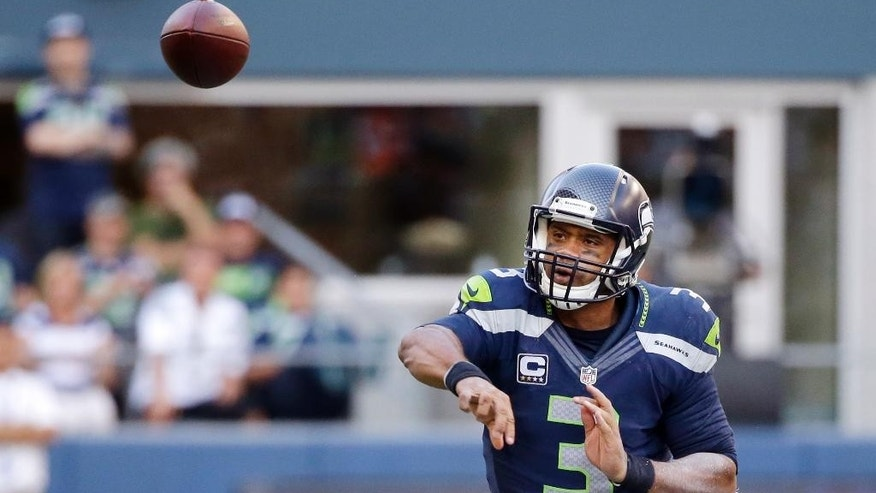 Seattle Seahawks quarterback Russell Wilson passes against the Denver Broncos in overtime in an NFL football game, Sunday, Sept. 21, 2014, in Seattle. The Seahawks won 26-20. (AP Photo/Elaine Thompson)