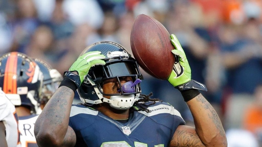 Seattle Seahawks' Marshawn Lynch reacts after rushing for a first down against the Denver Broncos in overtime of an NFL football game, Sunday, Sept. 21, 2014, in Seattle. The Seahawks won 26-20. (AP Photo/Elaine Thompson)