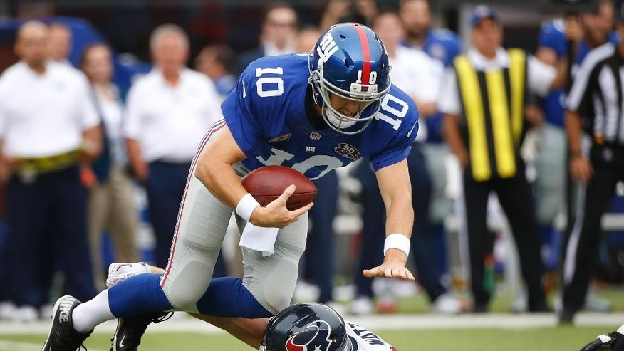 New York Giants quarterback Eli Manning (10) is tripped up for a sack by Houston Texans defensive end J.J. Watt (99) in the first quarter of an NFL football game, Sunday, Sept. 21, 2014, in East Rutherford, N.J. (AP Photo/Kathy Willens)