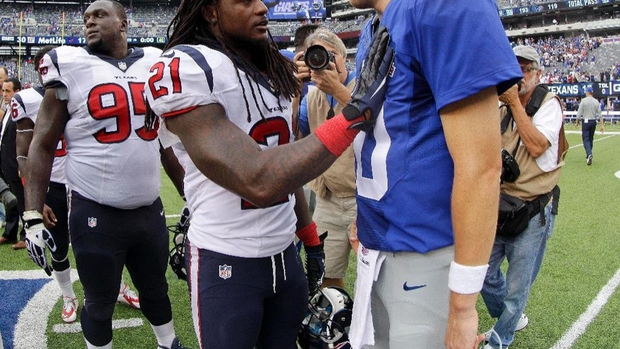 New York Giants quarterback Eli Manning (10) is greeted by Houston Texans free safety Kendrick Lewis (21) after the Giants beat the Texans 30-17 in an NFL football game, Sunday, Sept. 21, 2014, in East Rutherford, N.J. (AP Photo/Kathy Willens)