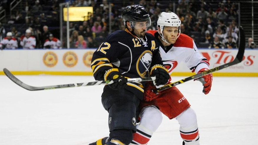Buffalo Sabres forward Brian Gionta (12) checks Carolina Hurricanes defenseman John-Michael Lilies (26) during the first period of an NHL hockey preseason game, Tuesday, Sept. 23, 2014, in Buffalo, N.Y. (AP Photo/Gary Wiepert)