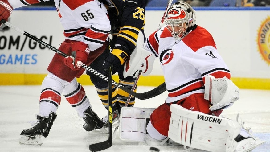 Carolina Hurricanes defenseman Ron Hainsey (65), battles with Buffalo Sabres forward Matt Moulson (26) as Hurricanes goaltender Anton Khudobin (31), of Kazakhstan, defends during the first period of an NHL hockey preseason game, Tuesday, Sept. 23, 2014, in Buffalo, N.Y. (AP Photo/Gary Wiepert)