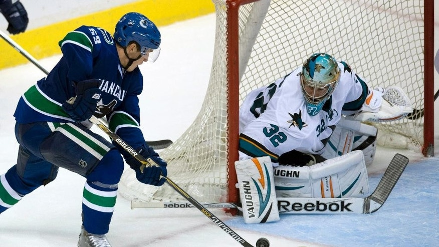 Vancouver Canucks Bo Hovat, left, tries to get a shot past San Jose Sharks goalie Alex Stalock (32) during the third period of an NHL preseason hockey game in Vancouver, British Columbia, Tuesday, Sept. 23, 2014. (AP Photo/The Canadian Press, Jonathan Hayward)