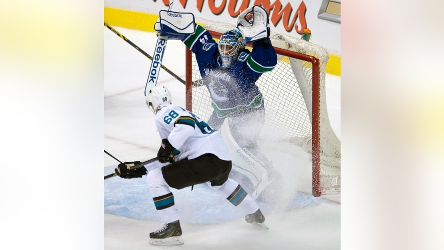 San Jose Sharks right wing Melker Karlsson (68) tries to get a shot past Vancouver Canucks goalie Joe Cannata (34) during the third period of an NHL preseason hockey game in Vancouver, British Columbia, Tuesday, Sept. 23, 2014. (AP Photo/The Canadian Press, Jonathan Hayward)
