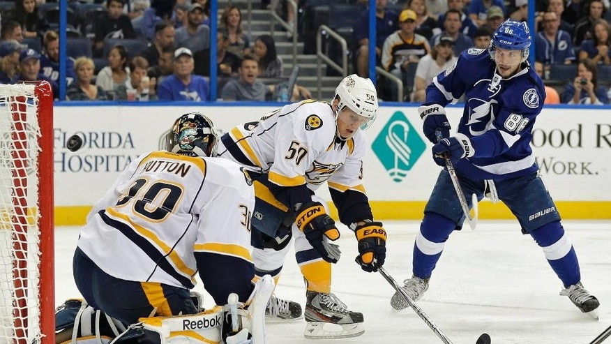 Tampa Bay Lightning right wing Nikita Kucherov (86), of Russia, shoots the puck past Nashville Predators defenseman Brian Lee (50) and goalie Carter Hutton (30) for a goal during the second period of an NHL preseason hockey game Tuesday, Sept. 23, 2014, in Tampa, Fla. (AP Photo/Chris O'Meara)