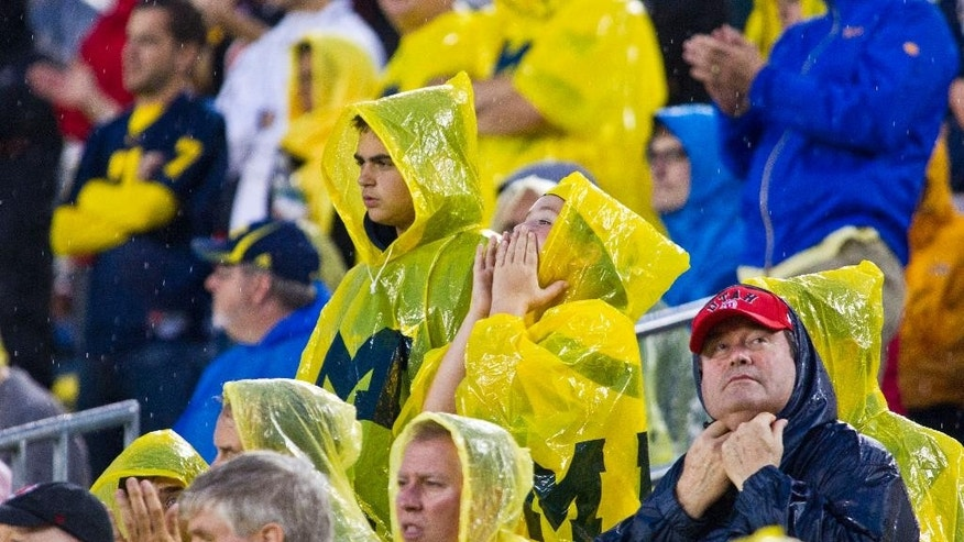 Michigan and Utah fans wear rain gear before inclement weather suspended a an NCAA college football game between the schools in the fourth quarter, in Ann Arbor, Mich., Saturday, Sept. 20, 2014. (AP Photo/Tony Ding)