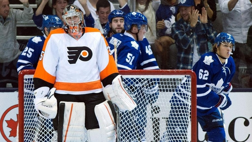 Philadelphia Flyers goaltender Steve Mason stands in goal as the Toronto Maple Leafs celebrate a goal by William Nylander, right, during the third period of a preseason NHL hockey game Tuesday, Sept. 23, 2014, in Toronto. (AP Photo/The Canadian Press, Frank Gunn)