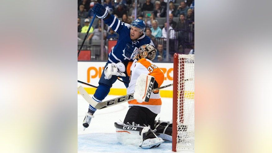 Toronto Maple Leafs' Leo Komarov collides with 'Philadelphia Flyers goaltender Steve Mason during the second period of a preseason NHL hockey game Tuesday, Sept. 23, 2014, in Toronto. (AP Photo/The Canadian Press, Frank Gunn)