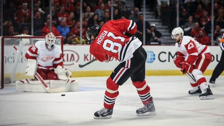 Chicago Blackhawks' Marian Hossa (81) shoots in the first period against the Detroit Red Wings goalie Jonas Gustavsson in an NHL exhibition hockey game in Chicago on Tuesday, Sept. 23, 2014. (AP Photo/Charles Cherney)