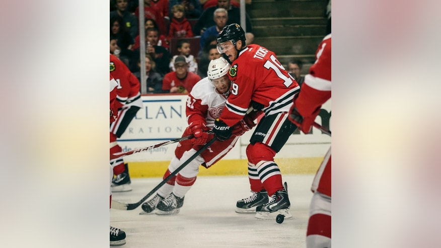 Chicago Blackhawks' Jonathan Toews battles the Detroit Red Wings' Luke Glendening, left, in an NHL exhibition hockey game in Chicago on Tuesday, Sept. 23, 2014. (AP Photo/Charles Cherney)