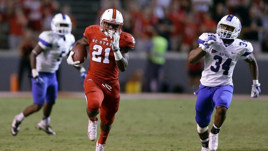 North Carolina State's Matt Dayes (21) runs for a touchdown as Presbyterian's Breyon Williams (34) chases during the second half of an NCAA college football game in Raleigh, N.C., Saturday, Sept. 20, 2014. North Carolina State won 42-0. (AP Photo/Gerry Broome)