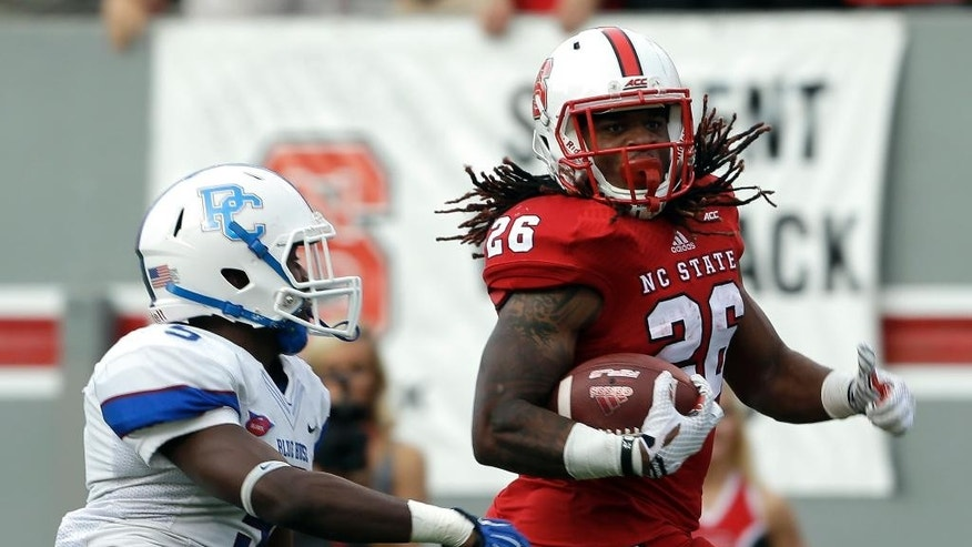 North Carolina State's Tony Creecy (26) runs the ball for a long gain as Presbyterian's Ed Britt (5) chases during the first half of an NCAA college football game in Raleigh, N.C., Saturday, Sept. 20, 2014. (AP Photo/Gerry Broome)