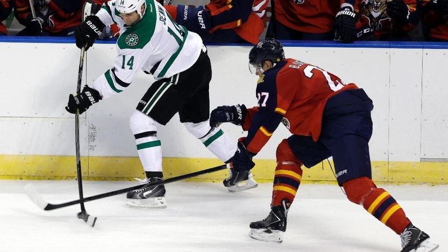Dallas Stars left wing Jamie Benn (14) prepares to pass as Florida Panthers center Nick Bjugstad (27) defends in the first period of an NHL hockey preseason game, in Sunrise, Fla., Wednesday, Sept. 24, 2014. (AP Photo/Alan Diaz)