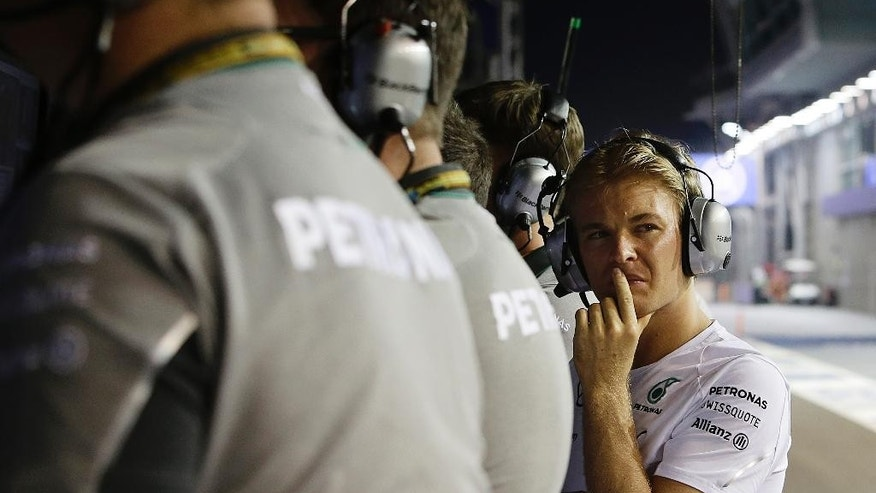Mercedes driver Nico Rosberg of Germany watches the race from the pit after retiring from the race due to car problems during the Singapore Formula One Grand Prix on the Marina Bay City Circuit in Singapore, Sunday, Sept. 21, 2014. (AP Photo/Tim Chong, Pool)