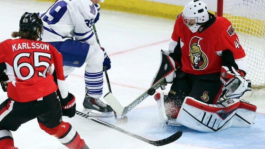 Ottawa Senators goaltender Craig Anderson, right, makes a save on Toronto Maple Leaf forward Matt Frattin (39) as Ottawa Senators defenceman Erik Karlsson (65) looks on during the first period of an NHL preseason hockey game in Ottawa, Ontario, on Wednesday, Sept. 24, 2014. (AP Photo/The Canadian Press, Fred Chartrand)