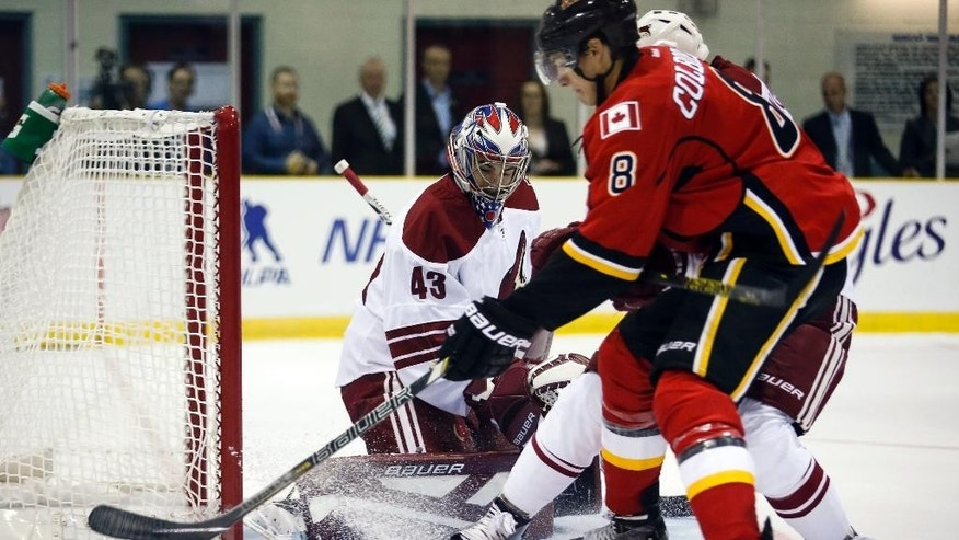 Arizona Coyotes goalie Mike McKenna, left, tracks the puck as Calgary Flames Joe Colborne tries for a rebound during the first period of an NHL preseason hockey game in Sylvan Lake, Alberta, Wednesday, Sept. 24, 2014. (AP Photo/The Canadian Press, Jeff McIntosh)