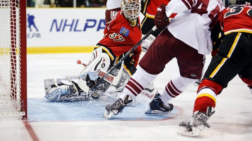 Arizona Coyotes forward B.J. Crombeen (44) scores on Calgary Flames goalie Joni Ortio during the second period of an NHL preseason hockey game in Sylvan Lake, Alberta, Wednesday, Sept. 24, 2014. (AP Photo/The Canadian Press, Jeff McIntosh)