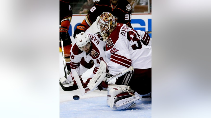 Arizona Coyotes goalie Louis Domingue blocks a shot as Jordan Martinook watches during the second period of an NHL hockey preseason game against the Anaheim Ducks in Anaheim, Calif., Tuesday, Sept. 23, 2014. (AP Photo/Chris Carlson)
