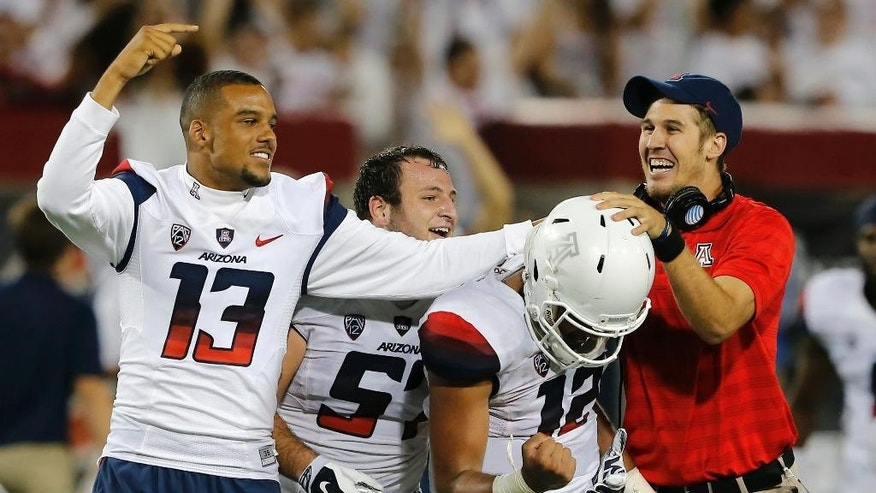 Arizona quarterback Anu Solomon (12) and Brandon Dawkins (13) celebrate after Solomon throws a hail mary touchdown during the second half of an NCAA college football game against California, Saturday, Sept. 20, 2014, in Tucson, Ariz. Arizona defeated California 49-45. (AP Photo/Rick Scuteri)